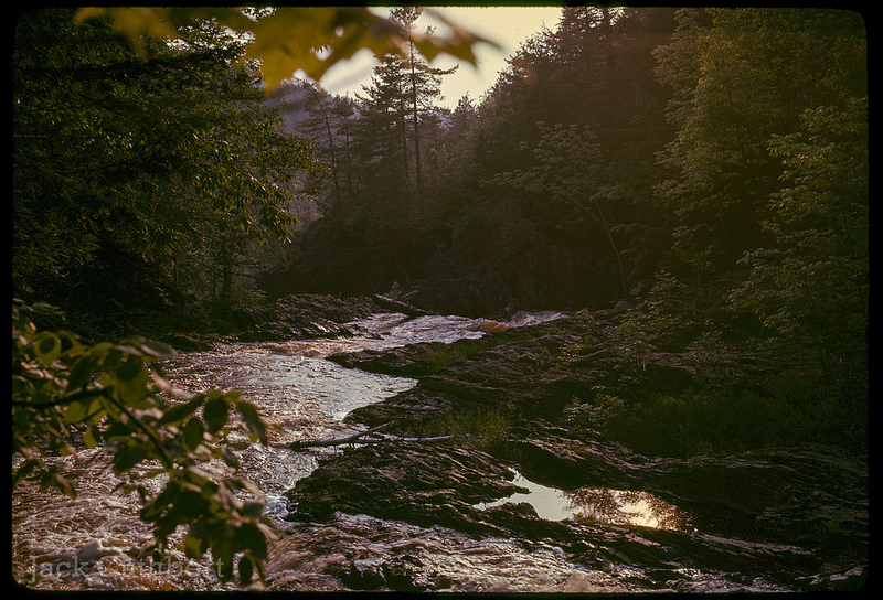 Photo of Rockville Notch, Nova Scotia, in 1961. Late afternoon, warm lighting, creek or small river passing through bottom of the frame.