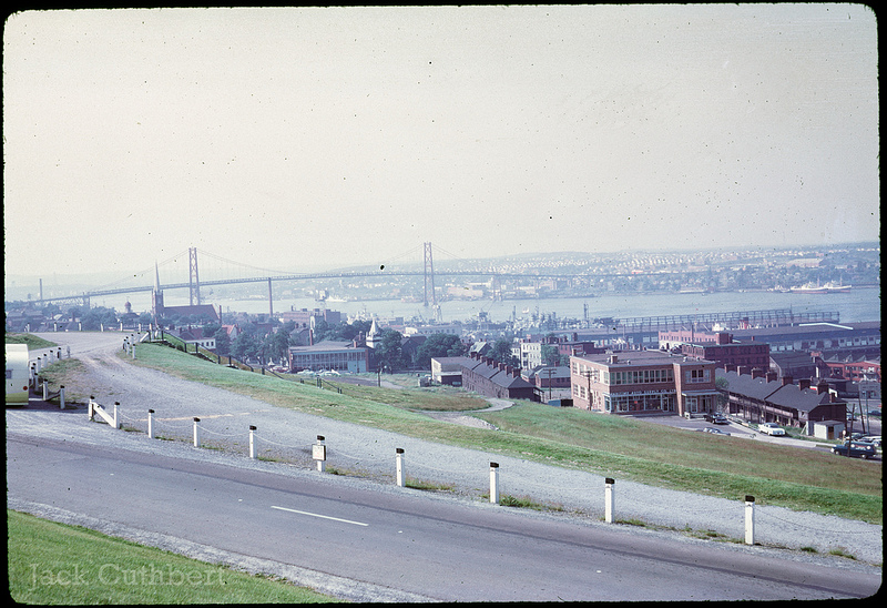 Photo of Halifax Harbour in 1961. Taken on a sunny day in the spring or summer months. Vantage shows buildings below along river and harbour. Bridge crossing river in the background.