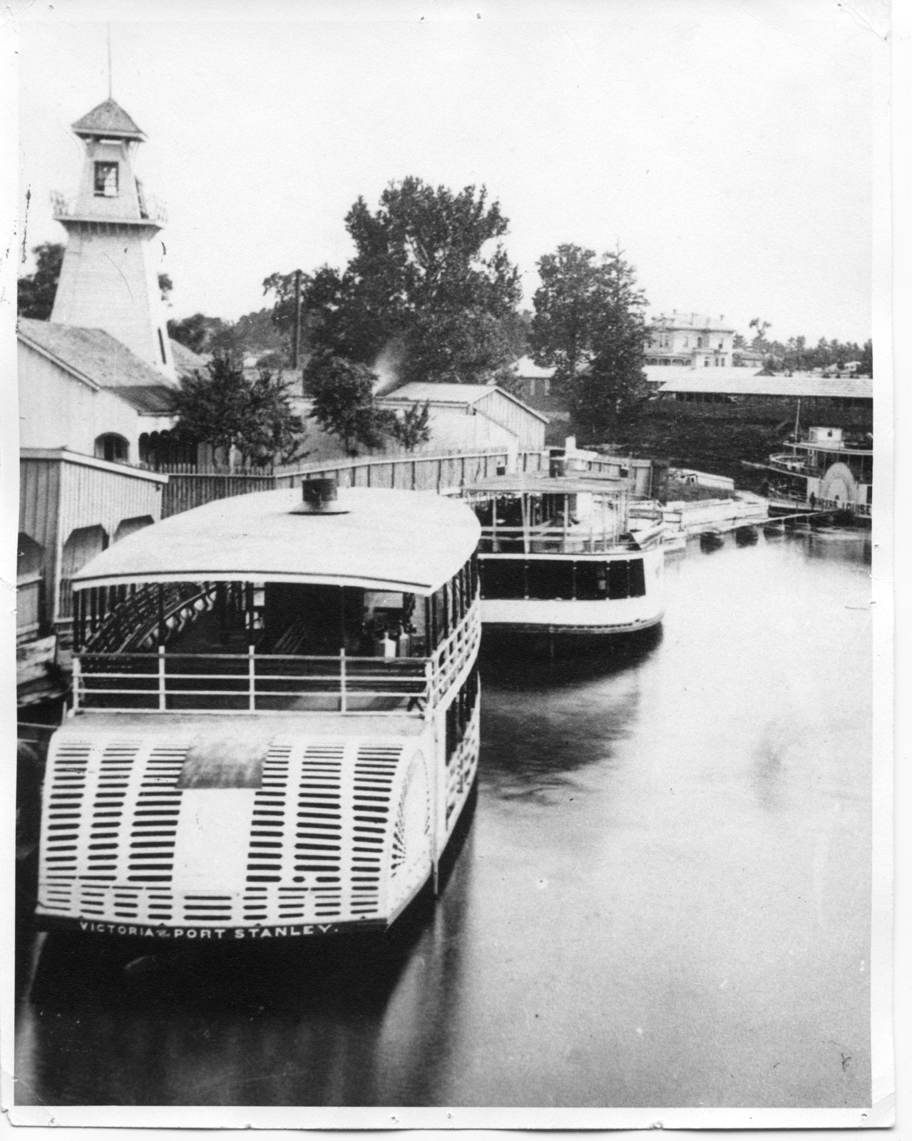 """A black and white print of boats docked at the River Excursion Boat Terminal at the forks of the Thames. The Victoria is in the foreground. The words """"Victoria Port Stanley"""" are painted on the stern. Large lanterns, used during moonlight rides, can be seen on the right deck of the Victoria. In the right background is the Princess Louise. The steam tower at the Sulphur Springs can be seen on the left. (Cairncross Collection, Ivey Family London Room, London Public Library)"""